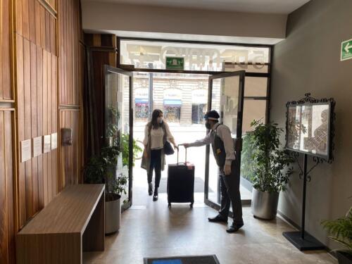 mujer entrando a un hotel con maleta