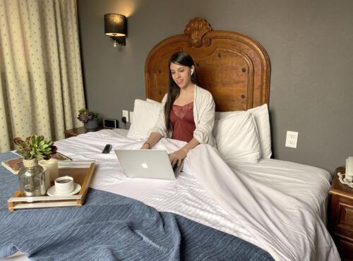 mujer sobre la cama con una laptop