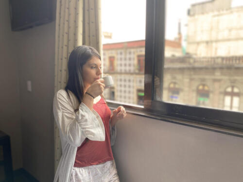 mujer tomando cafe, mirando por la ventana